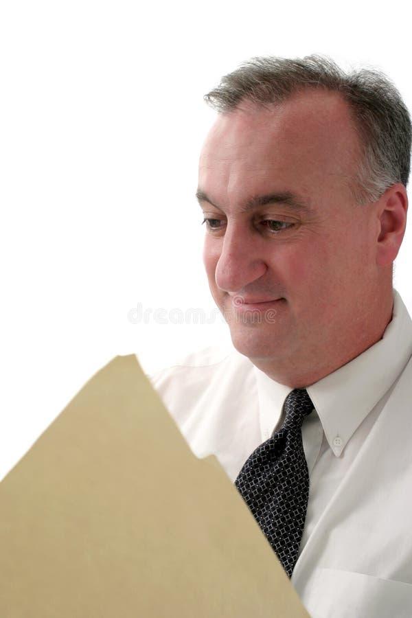 Informe sonriente de la lectura del hombre de negocios imagen de archivo