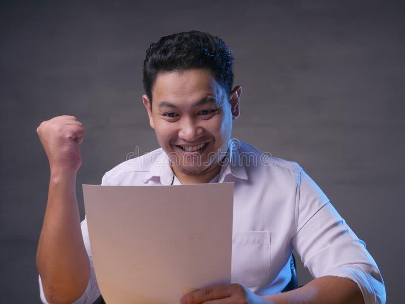 Informe sorprendido sonriente feliz de Reading Positive Financial del hombre de negocios imágenes de archivo libres de regalías