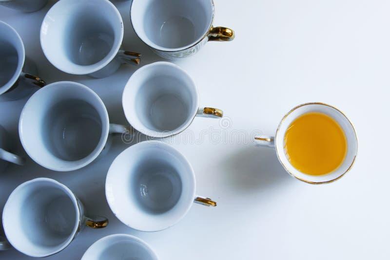 Informeer anderen Een concept van koffiekoppen, één hoogtepunt van `-ideeën ` die en andere leeg wordt vertegenwoordigd stock afbeeldingen