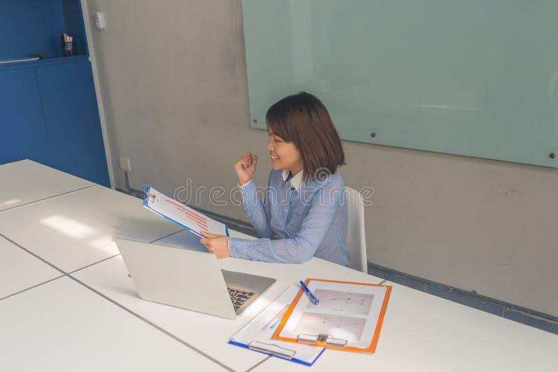 Informes financieros de lectura de la empresaria asiática acertada y sentir feliz foto de archivo