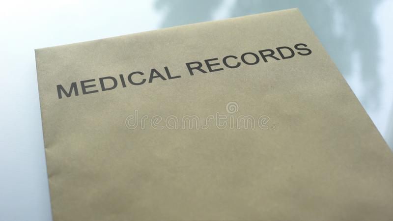 Informes médicos, carpeta con los documentos importantes que mienten en la tabla, cierre para arriba imagen de archivo libre de regalías