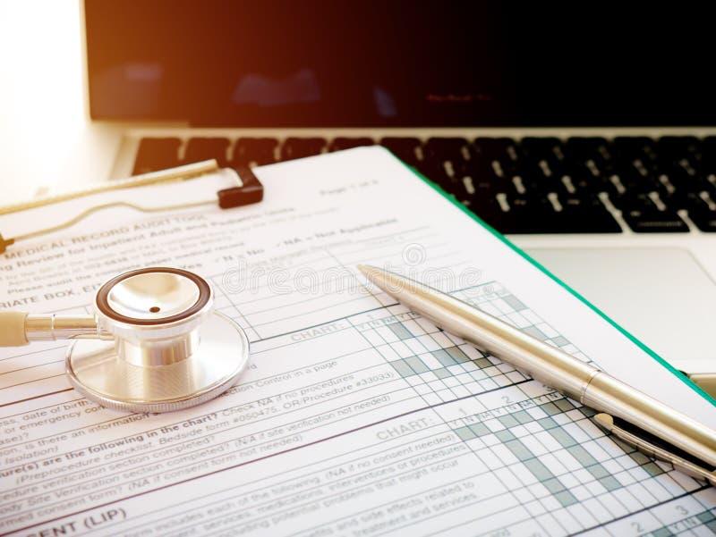 Informes médicos, estetoscopio y ordenador portátil foto de archivo libre de regalías