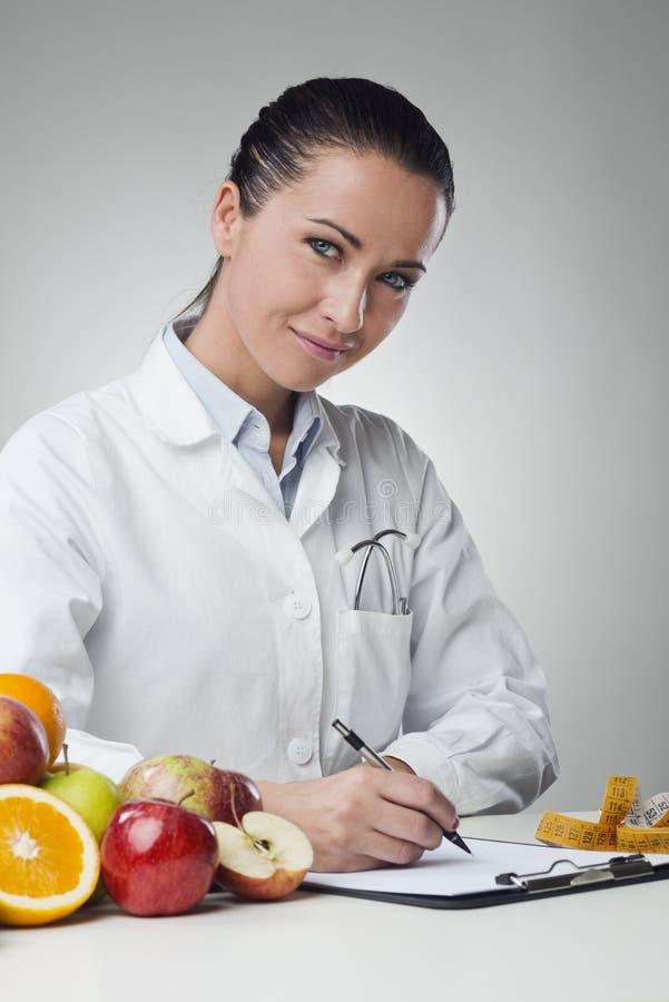 Informes médicos sonrientes de la escritura del nutricionista imagen de archivo libre de regalías