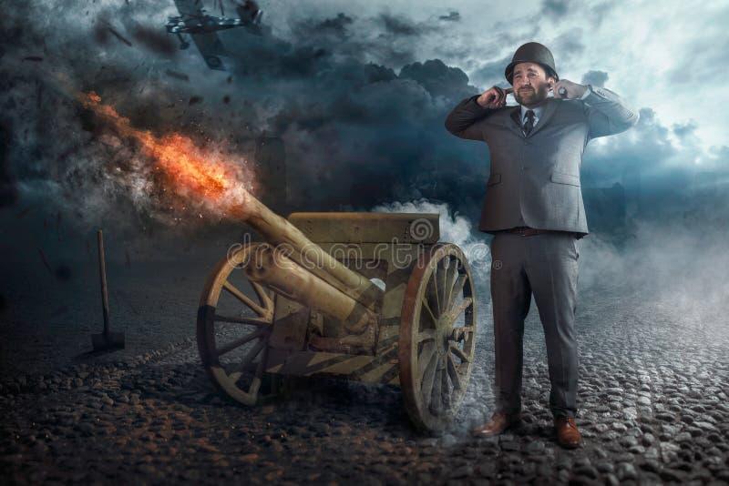 Infornamento dell'uomo d'affari con il vecchio cannone fotografia stock libera da diritti