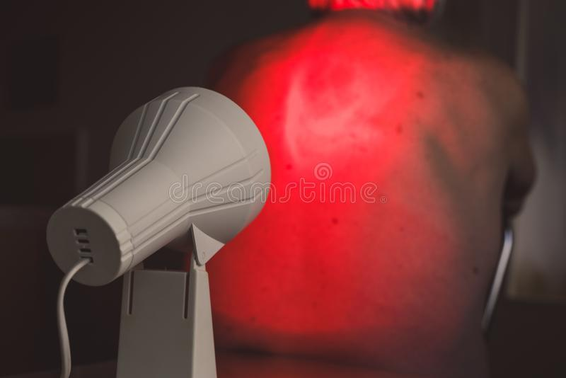 Infrared radiation therapy. Infrared radiation heat light lamp therapy. Senior back pain royalty free stock images
