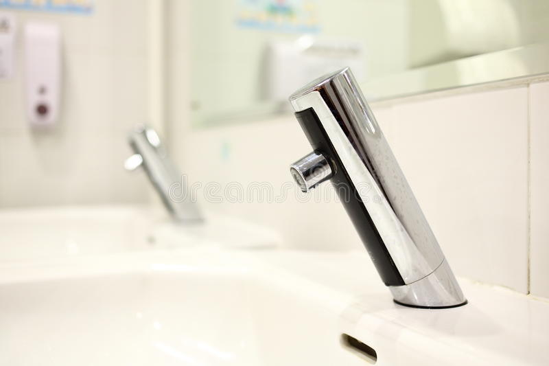 Infrared Faucet. Infrared sensor faucet in a washroom royalty free stock image