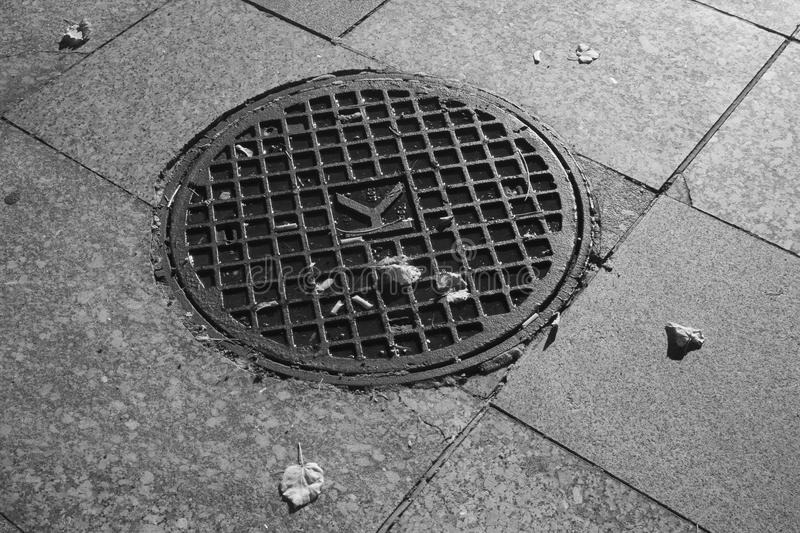 Infrared shot of round metal manhole cover. On tiled pavement stock photography