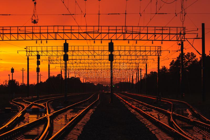 Infrastructure ferroviaire de silhouettes foncées dans le coucher du soleil dramatique Backl photos libres de droits