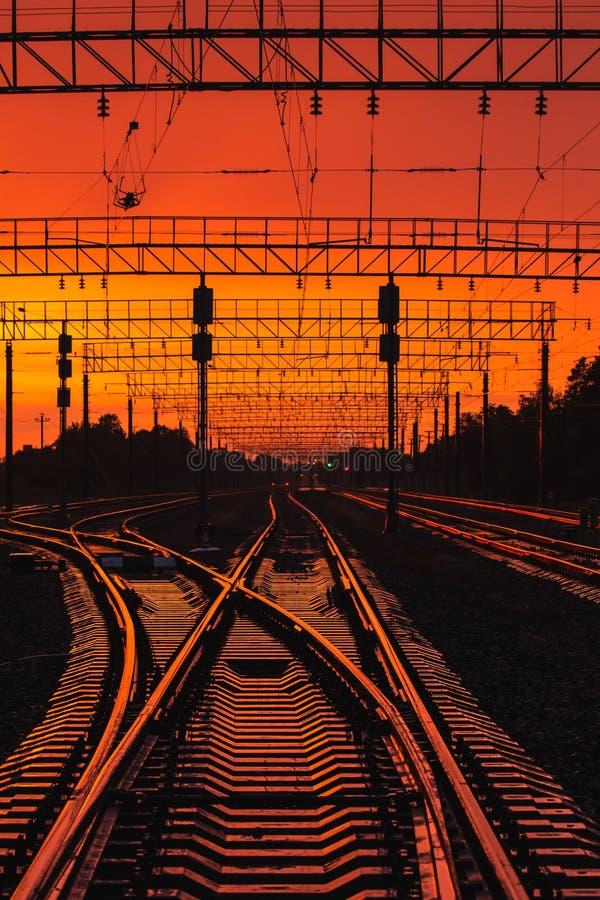 Infrastructure ferroviaire de silhouettes foncées dans le coucher du soleil dramatique Backl photo stock