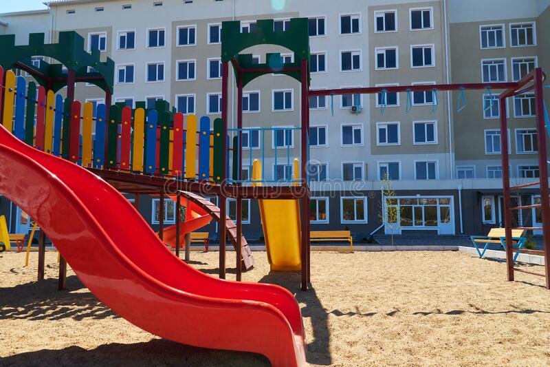 Infrastructure résidentielle urbaine sans personne - aire de jeux pour enfants à côté d'un condominium Swing, toboggan, escaliers photos libres de droits