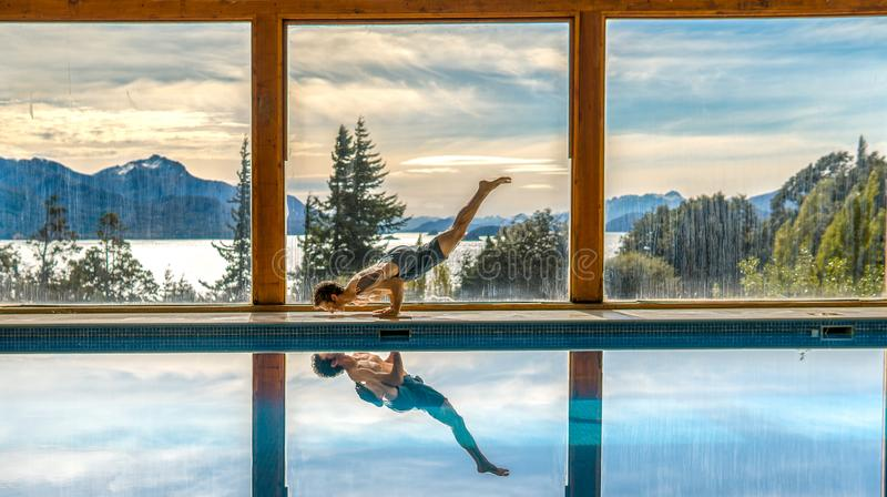 Yoga Poses by Pool. Infront of mountains and lake with reflection in pool, landscape, nature, active, adult, arm, asana, body, concentration, exercise, fit royalty free stock images