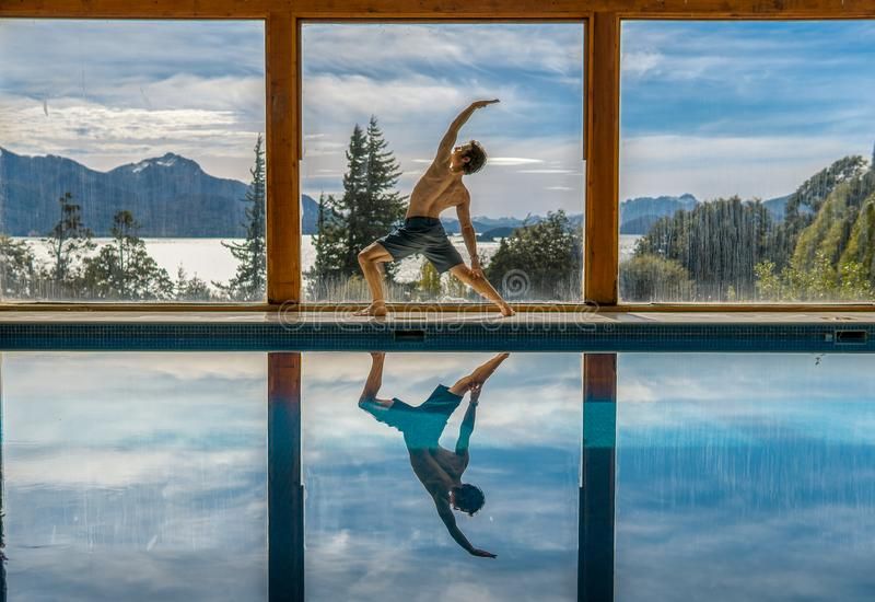 Yoga Poses by Pool. Infront of mountains and lake with reflection in pool, landscape, nature, active, adult, arm, asana, body, concentration, exercise, fit stock images