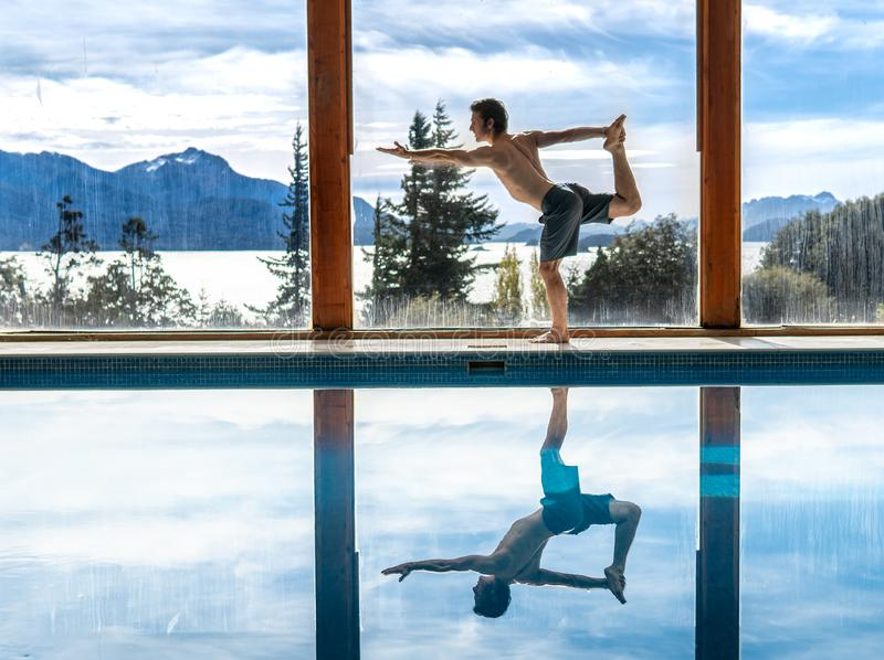 Yoga Poses by Pool. Infront of mountains and lake with reflection in pool, landscape, nature, active, adult, arm, asana, body, concentration, exercise, fit stock image