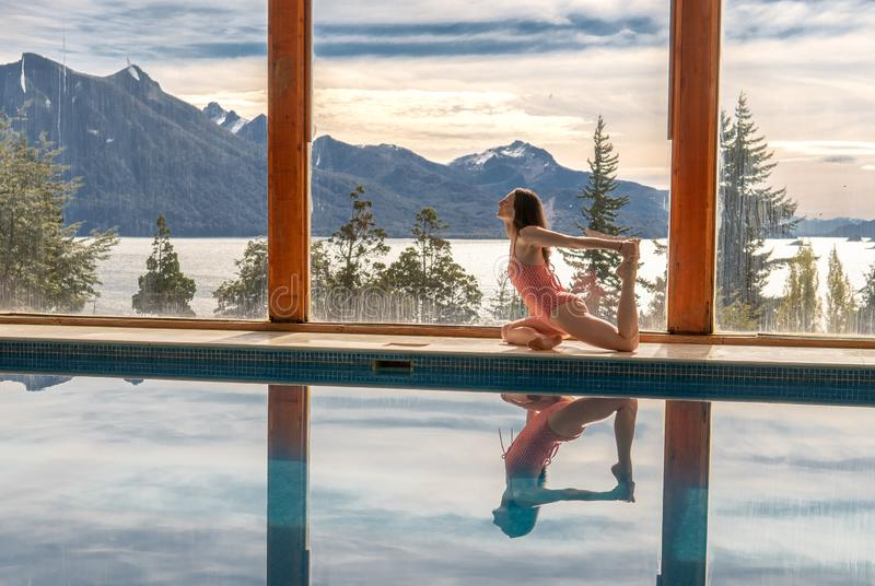 Yoga Poses by Pool. Infront of mountains and lake with reflection in pool, landscape, nature, outdoors, adult, ashtanga, beautiful, blue, body, concentration stock photos