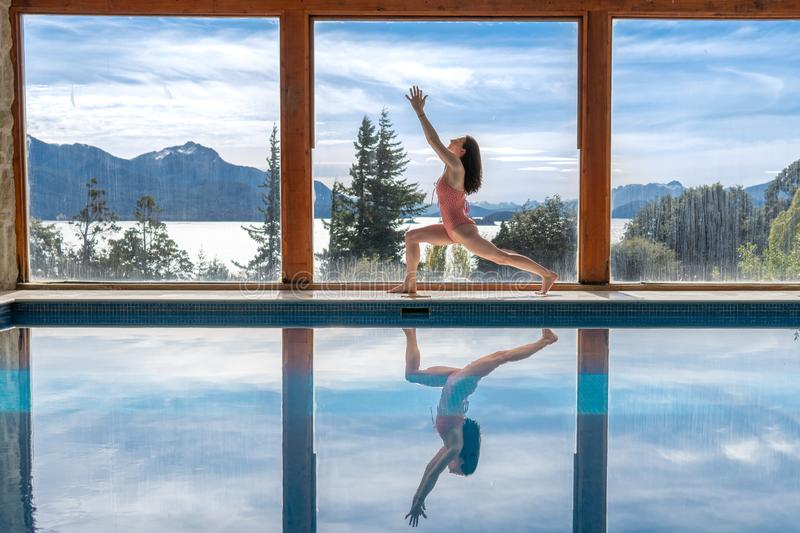 Yoga Poses by Pool. Infront of mountains and lake with reflection in pool, landscape, nature, outdoors, adult, ashtanga, beautiful, blue, body, concentration royalty free stock photo