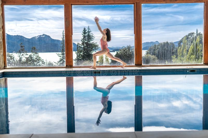 Yoga Poses by Pool. Infront of mountains and lake with reflection in pool, landscape, nature, outdoors, adult, ashtanga, beautiful, blue, body, concentration stock photo