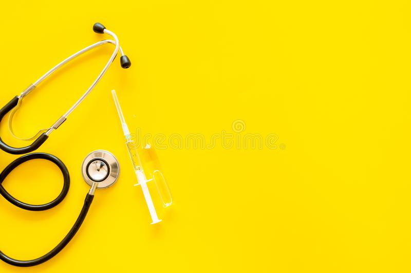 Infuenza, flu vaccine in syringe near stethoscope on yellow background top viewspace for text. Infuenza, flu vaccine in syringe near stethoscope on yellow stock photo