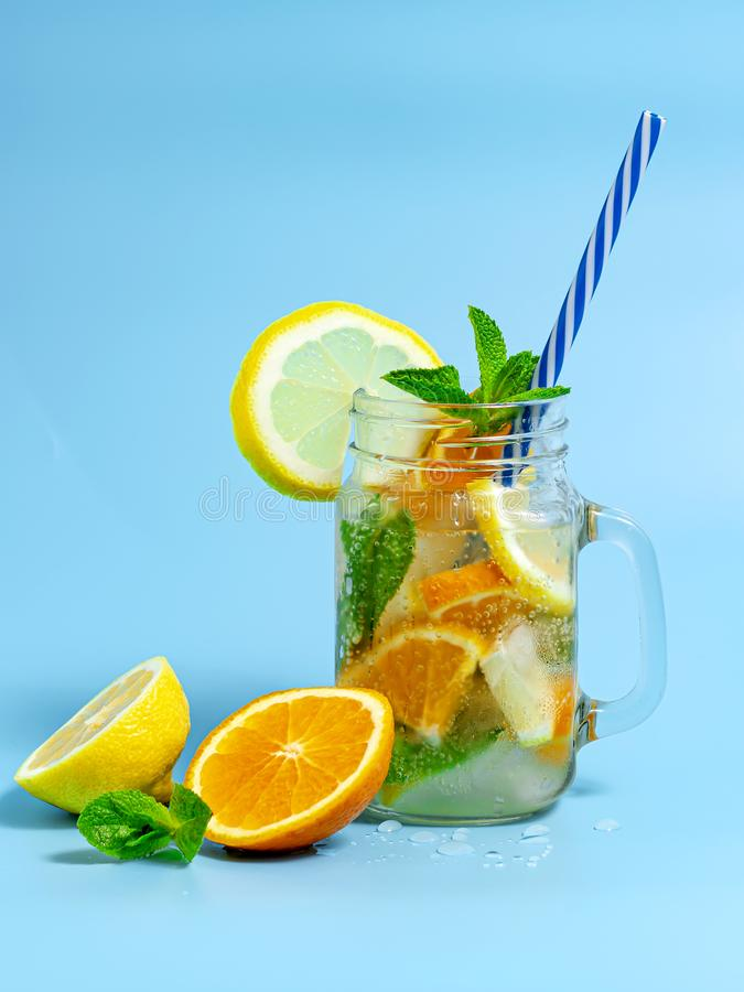 Infused detox water with ice, lemon and oranges slices with mint on blue background. Iced cold summer cocktail or lemonade in royalty free stock images