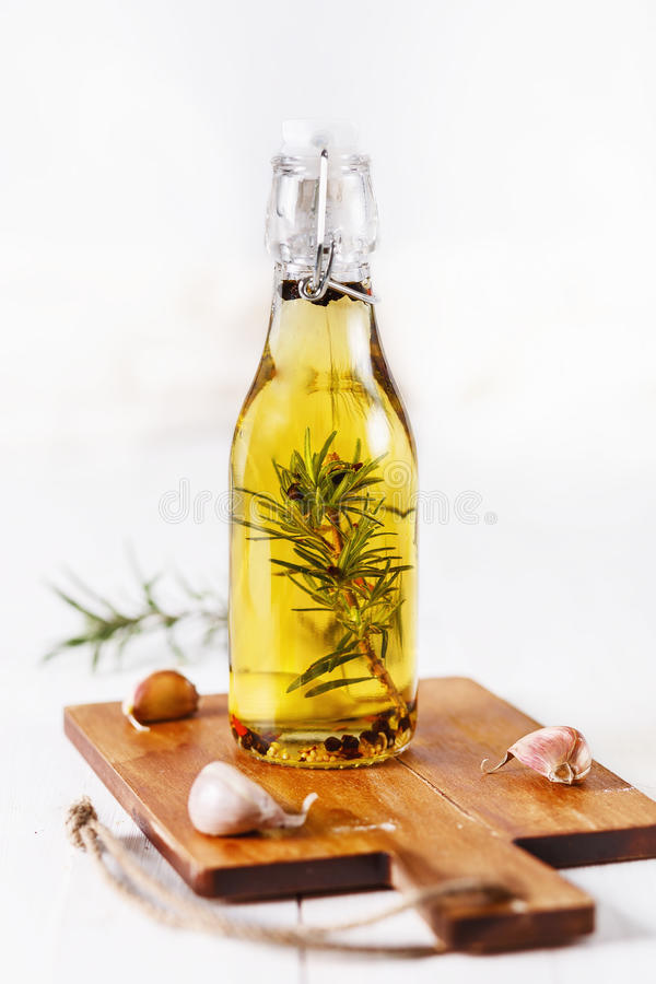 Infused olive oil over white wooden background royalty free stock image