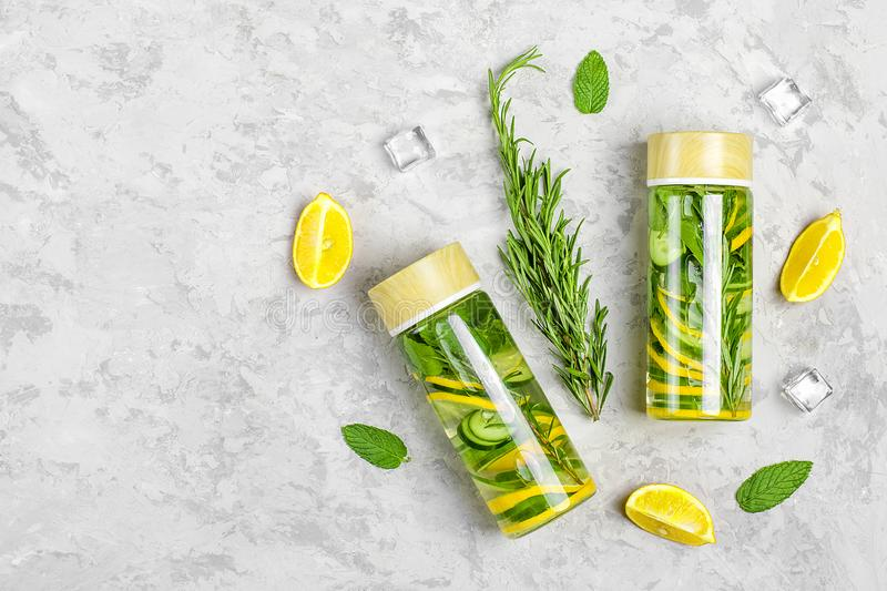 Infused water, cocktail, lemonade or tea. Summer iced cold drink with lemon, tarragon, lime, cucumber and leaf of mint on gray con stock image