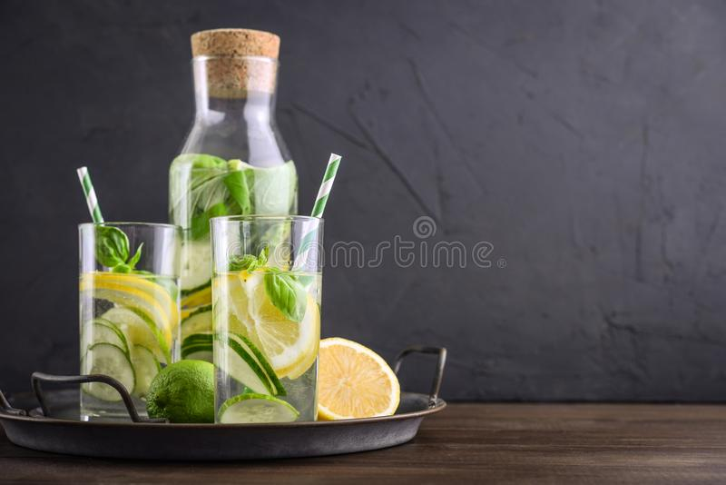 Infused water with cucumber, lemon, lime and basil. In glass on tray on black background royalty free stock photos