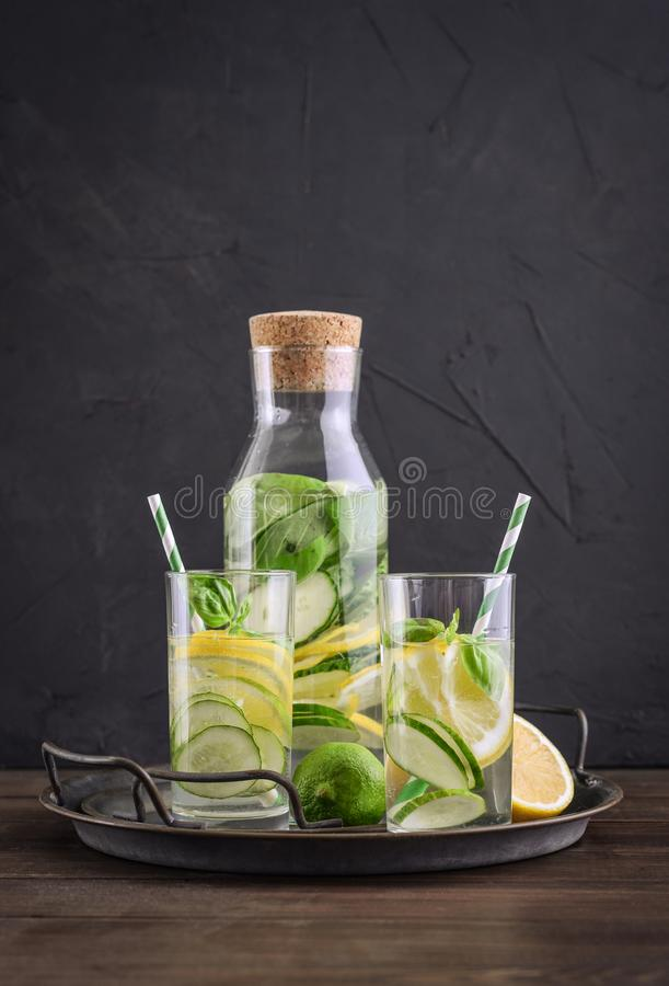 Infused water with cucumber, lemon, lime and basil. In glass on tray on black background royalty free stock image
