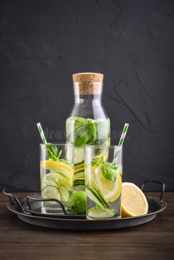 Infused water with cucumber, lemon, lime and basil. In glass on tray on black background stock image