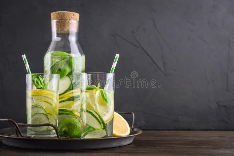 Infused water with cucumber, lemon, lime and basil. In glass on tray on black background stock images