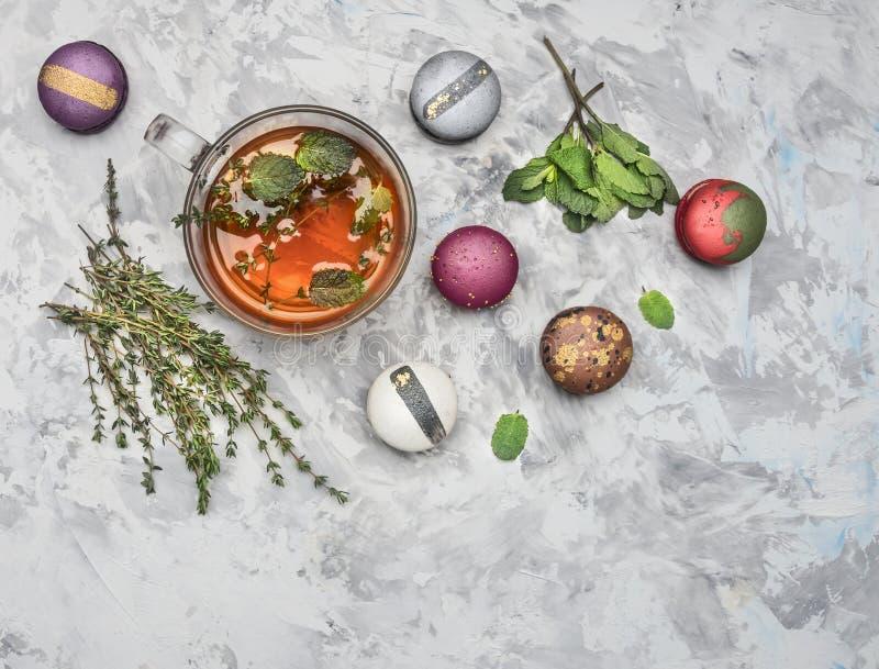 Infusión de hierbas caliente con la menta, el comino y los macarrones apetitosos frescos, en el fondo rústico blanco, visión supe imagen de archivo libre de regalías