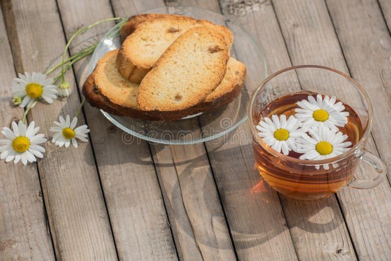 Infusión de hierbas con las margaritas y los bizcochos tostados en una placa de cristal en un t de madera fotografía de archivo libre de regalías