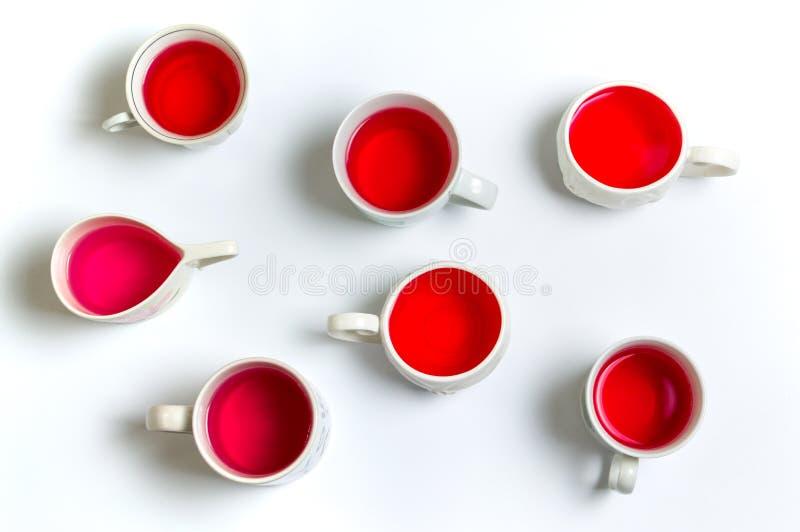 Infusión de hierbas roja en tazas en el fondo blanco imagen de archivo libre de regalías
