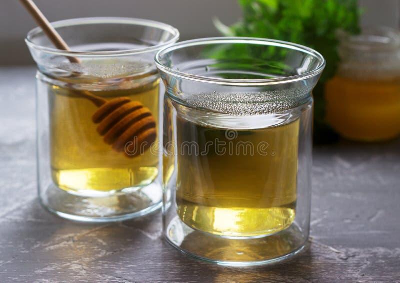 Infusi?n de hierbas hecha de b?lsamo de la menta y de lim?n con la miel en las tazas de cristal Estilo r?stico foto de archivo libre de regalías