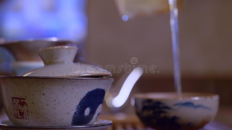 Infusione di versamento matrice del tè dalla ciotola di imparzialità in tazza Cerimonia di tè cinese fotografia stock