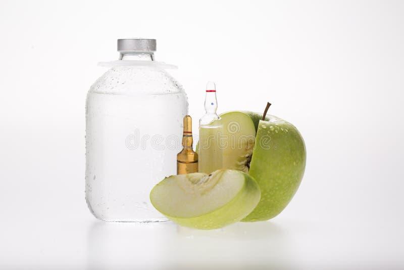 Infuzi butelka, ampule, zielony jabłko na białym backgroun obraz royalty free