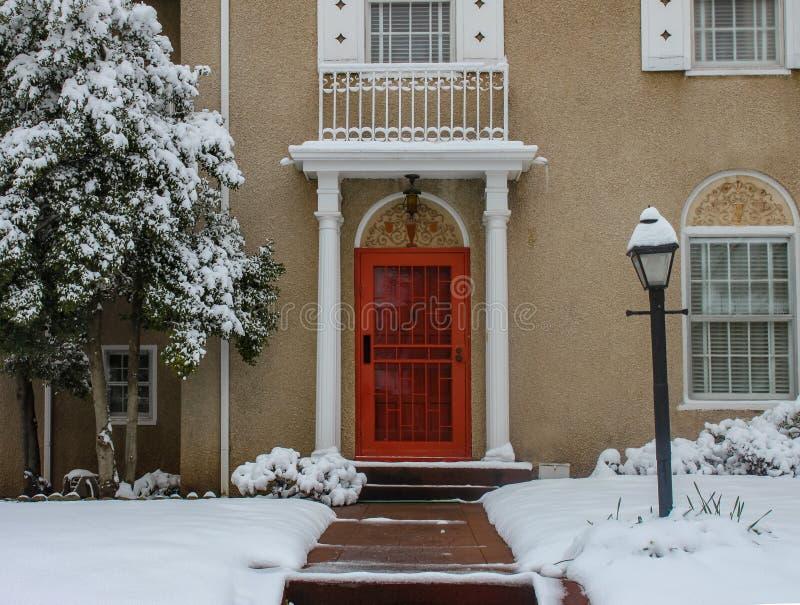 Ingång av det eleganta exklusiva stuckaturhuset med pelare och tegelplattor i snö med den ljusa röda dörren royaltyfria bilder