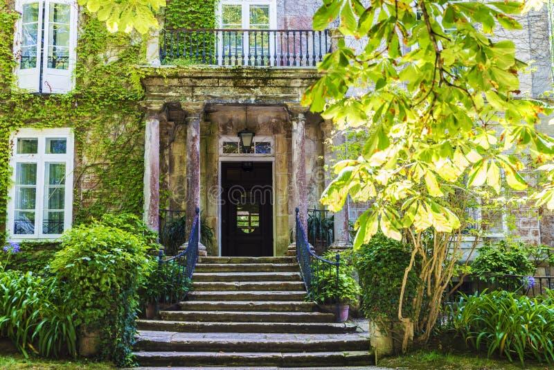 Ingång av en gammal herrgård med trädgården royaltyfria foton