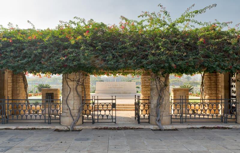 Ingång av kyrkogården för Heliopolis brittiska samväldetkrig med staketmetalldörren, gröna växter för klättrare, Kairo, Egypten royaltyfria foton