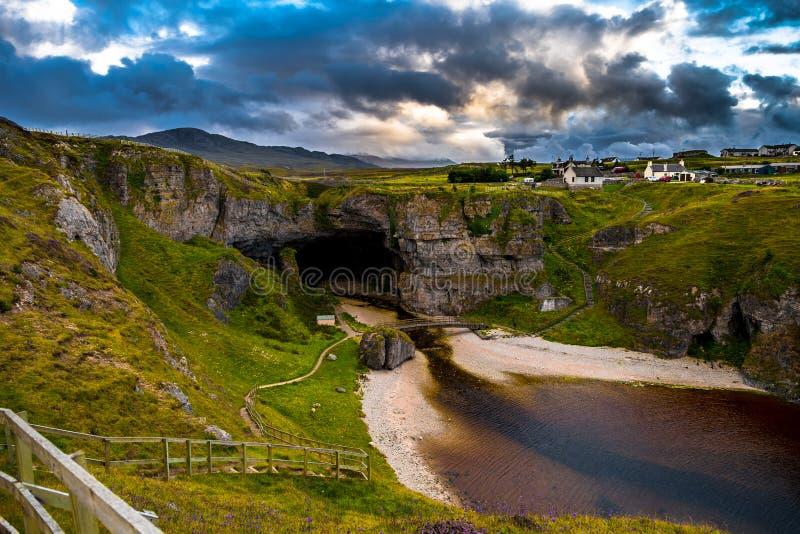 Ingång och bana med bron till den Smoo grottan nära Durness i Skottland royaltyfria bilder