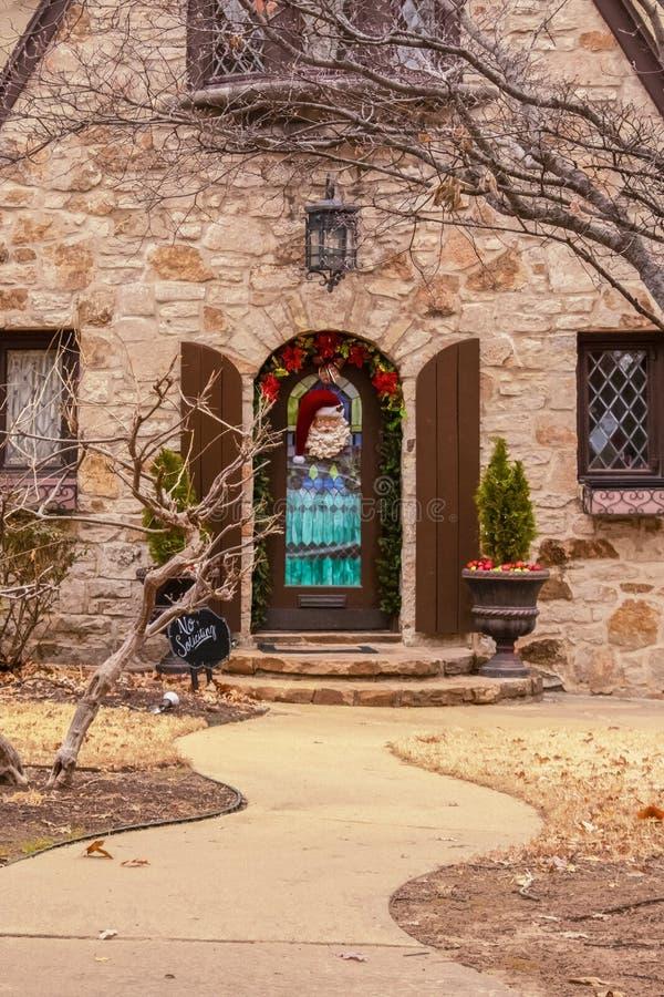 Ingång som vaggar huset med den nätt jul dekorerade ytterdörren och den buktiga trottoaren royaltyfria bilder