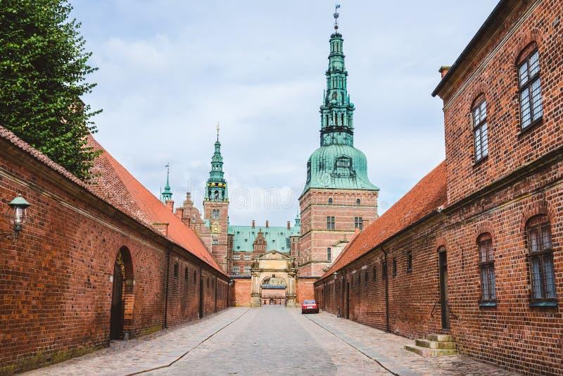 Ingång till den Frederiksborg slotten i Köpenhamnen, Danmark - September, 24th, 2015 Fästningvägg för röd tegelsten och gräsplank arkivfoto