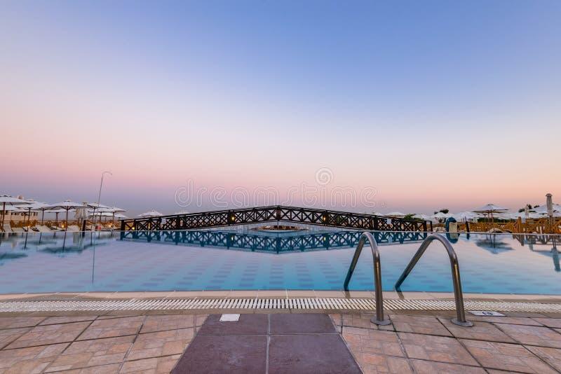 Ingång till simbassängen på hotellsemesterorten, blå timme för soluppgång, Rhode, Grekland royaltyfri fotografi