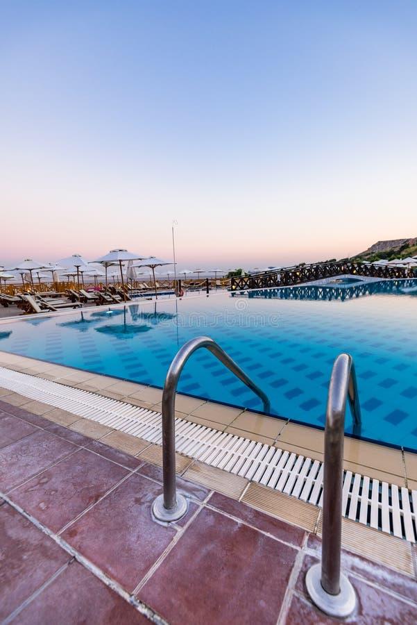 Ingång till simbassängen på hotellsemesterorten, blå timme för soluppgång, Rhode, Grekland royaltyfri foto