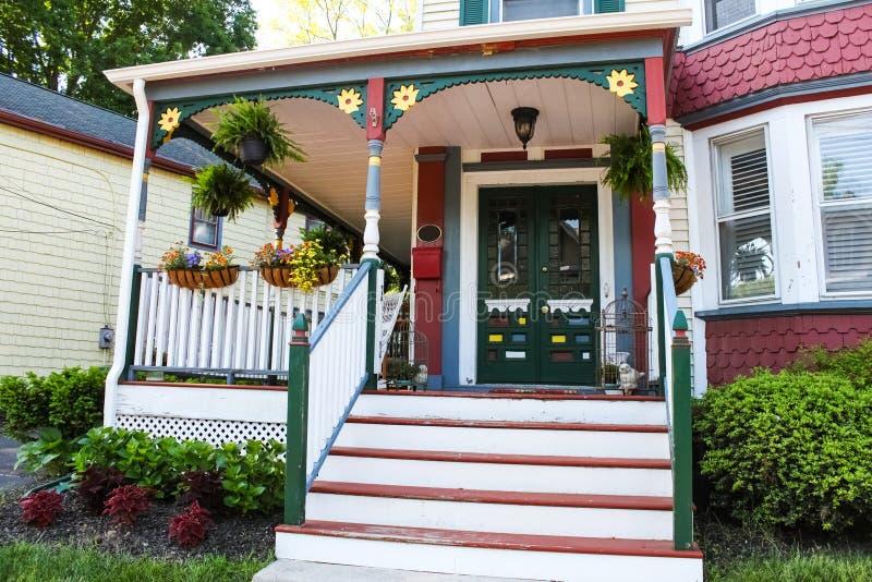 Ingången av det gamla utsmyckade huset för pepparkakavictorianstil dekorerade för sommar med blommor och farstubrodekoren royaltyfria bilder