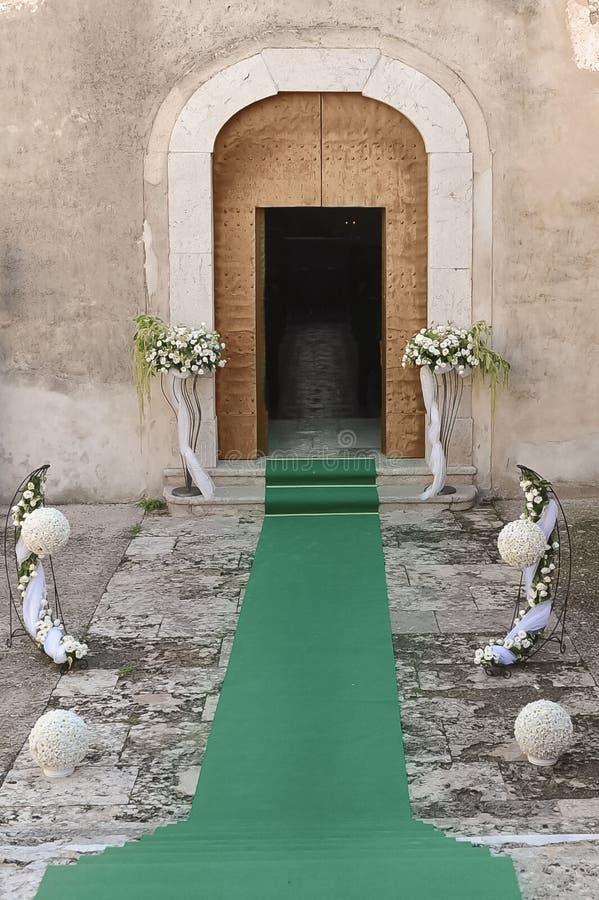 Ingången av en kyrka dekorerade med socklar av blommor och ett G royaltyfria bilder