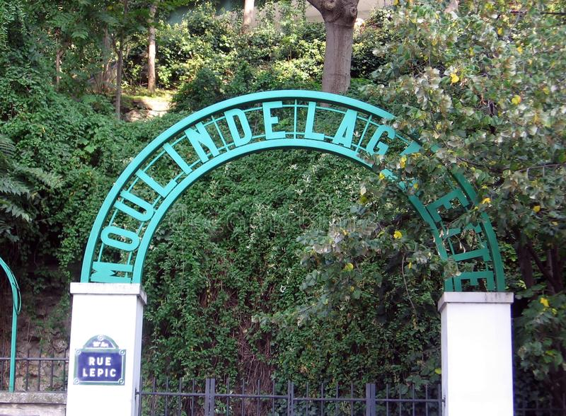 Ingången till Moulinen de la Galette är en väderkvarn som lokaliseras i hjärtan av Montmartre, var den krönar den mest berömda ku arkivfoto