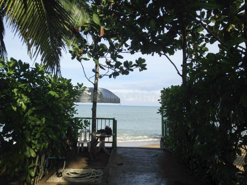 Ingången till stranden, gömma i handflatan, paraplyer, kopplar av, semestertid arkivbilder