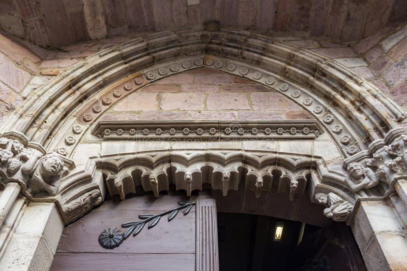 Ingångsdörr av Notre-Dame-du-Anfall-du-Pont Kyrktaga i Helgon-Jean-Pied-de-port, Frankrike, arkitektonisk detalj royaltyfria foton