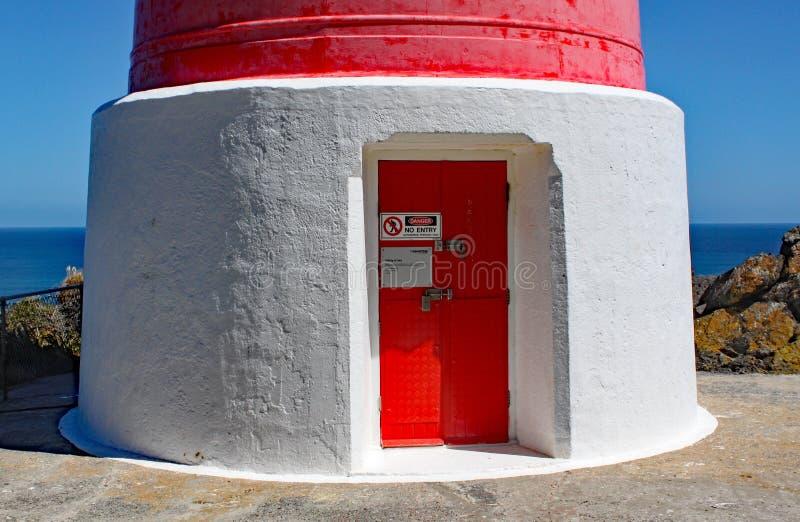 Ingångsdörren av den röda och vita randiga fyren på udde Palliser på den norr ön, Nya Zeeland Ljuset byggdes in royaltyfri bild