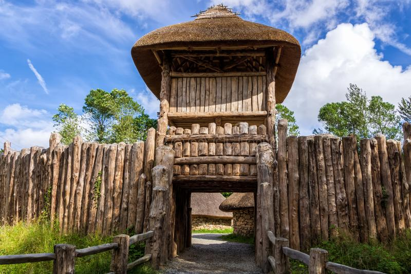 Ingångshoporten i palissad- och vakttorn till gammalt halmtäcker och stenar stugan royaltyfria foton