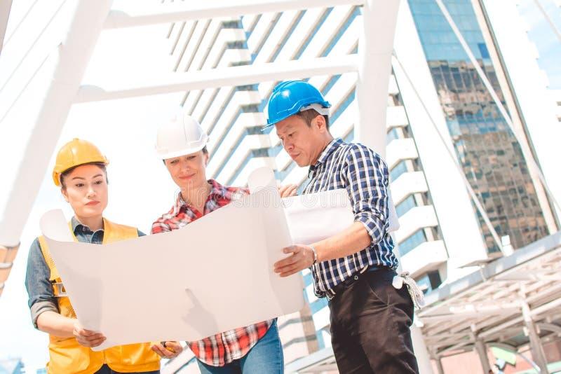 Ingénierie de casque de sécurité d'usage de l'ingénieur industriel trois fonctionnant et parlant avec l'inspection de dessins images stock